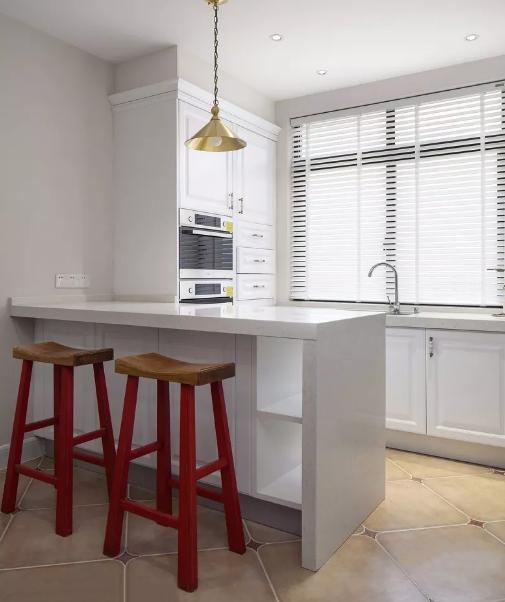 餐桌椅后方设计了吧台与西厨区,台面和地砖的颜色都很浅,加上从窗户外涌入的充足光线。