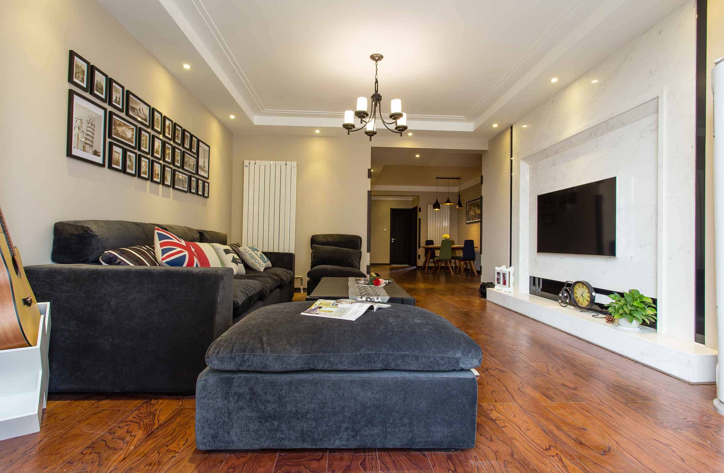 客厅的地面整个以木质为铺贴,顶面则是以白色的乳胶漆刷至而成,整个贞洁雅致之感