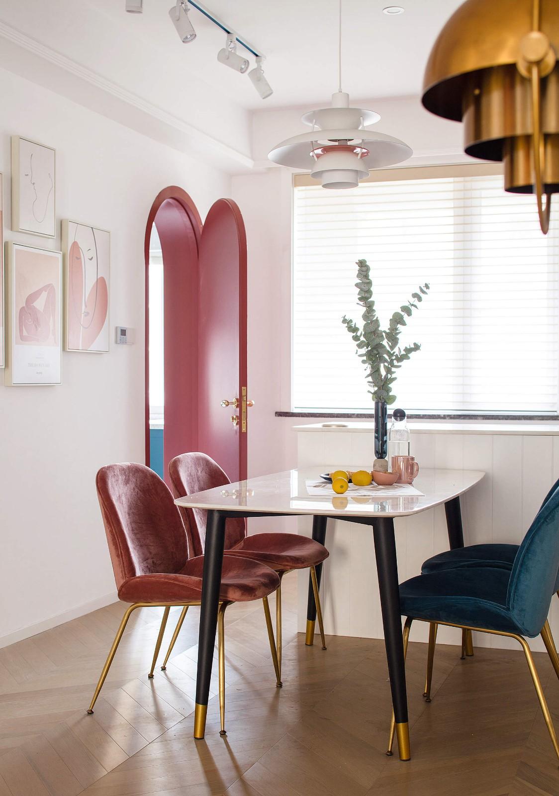 餐厅靠近窗户,采光很好,大理石桌面的餐桌紧靠吧台,搭配红色、蓝色餐椅,简约时尚。