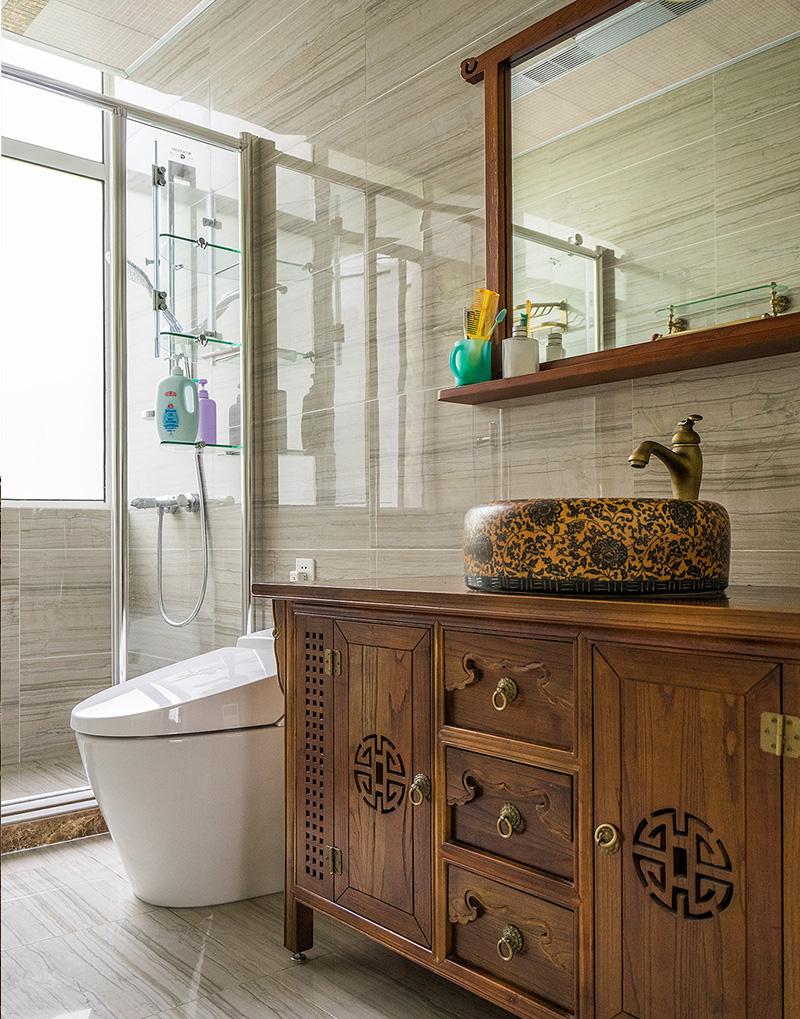 卫生间干湿两块部分,洗手盆是相对来说湿度比较小的区域,所以也采用了和整体风格一致的木质矮柜。