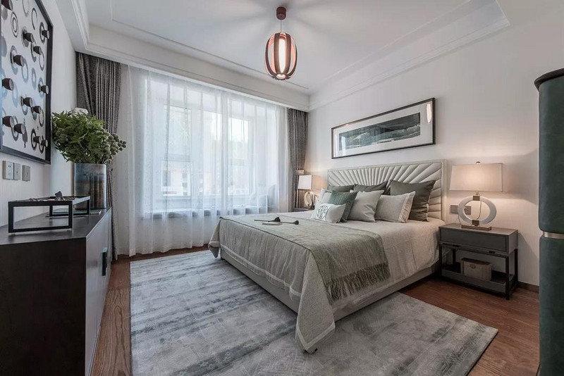素净的墙面基础上,以简单的家居布置,在橄榄状的吊灯下打造出低调但轻奢的卧室空间。