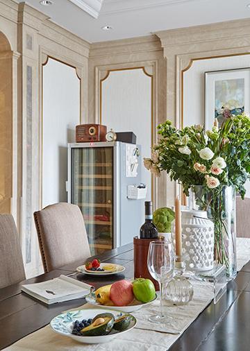 长而宽敞的餐桌,搭配简约的米色餐布和鲜活的花卉,让用餐空间充满温馨感和生机。
