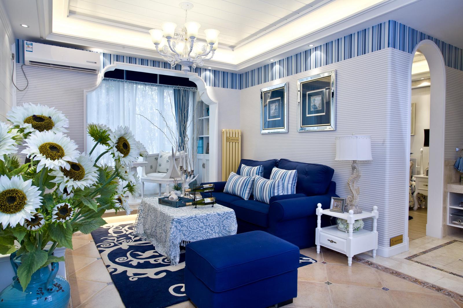 客厅布局比较紧凑,白色怀旧的文化石电视背景墙装饰,蓝色的地毯和绿色的植物摆放营造温馨的氛围