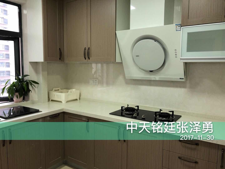 原木色橱柜设计简单自然,圆形油烟机造型时尚,窗户设计有助于厨房的空气流通,促进油烟的散发。