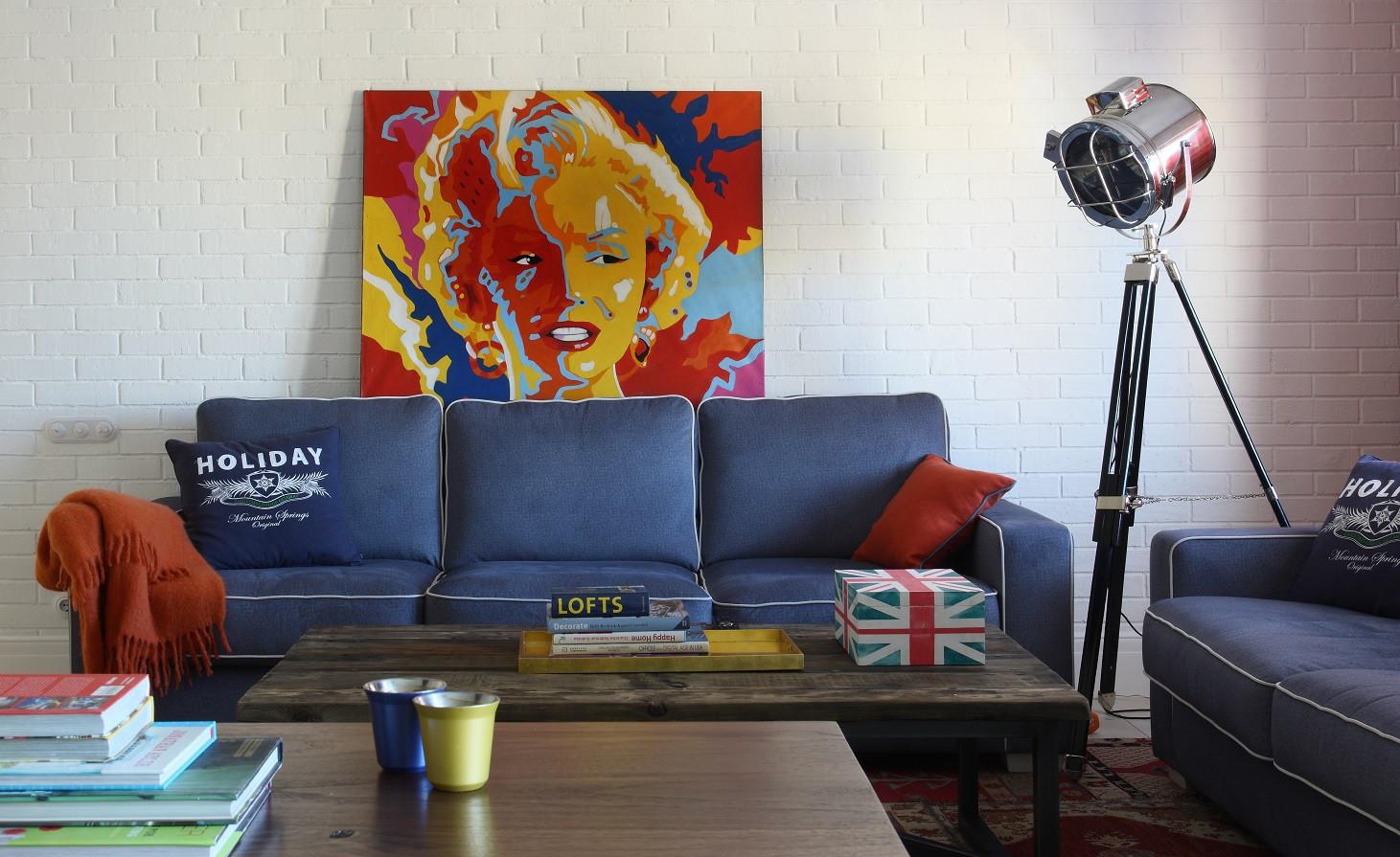 客厅摆放着蓝色的沙发,以及沙发的背景墙放置着炫彩的画,点缀着整个客厅的艺术气息
