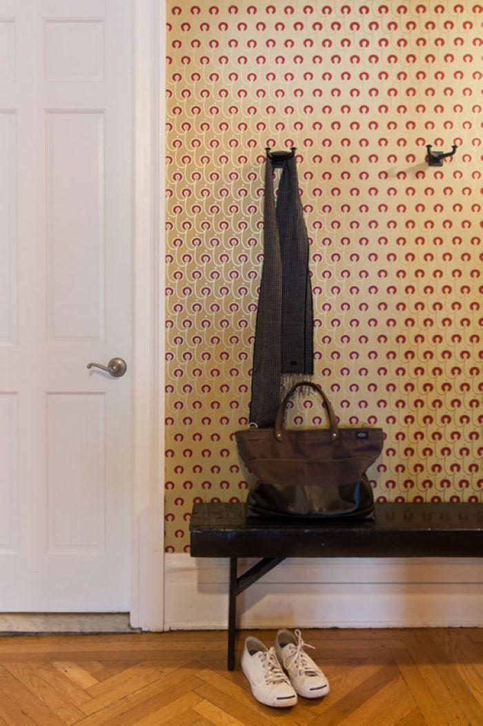 玄关处墙面贴了带图案的壁纸,一个换鞋凳和挂衣钩满足了基本的收纳功能。