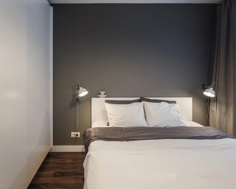 在卧室的墙面定制了整面的储物柜,从而轻松解决了衣物的收纳问题,素雅的色彩搭配,让木色的墙面装饰显得十