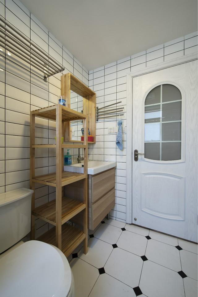 卫生间也同样用白色来增加视野范围,木色置物架方便实用。