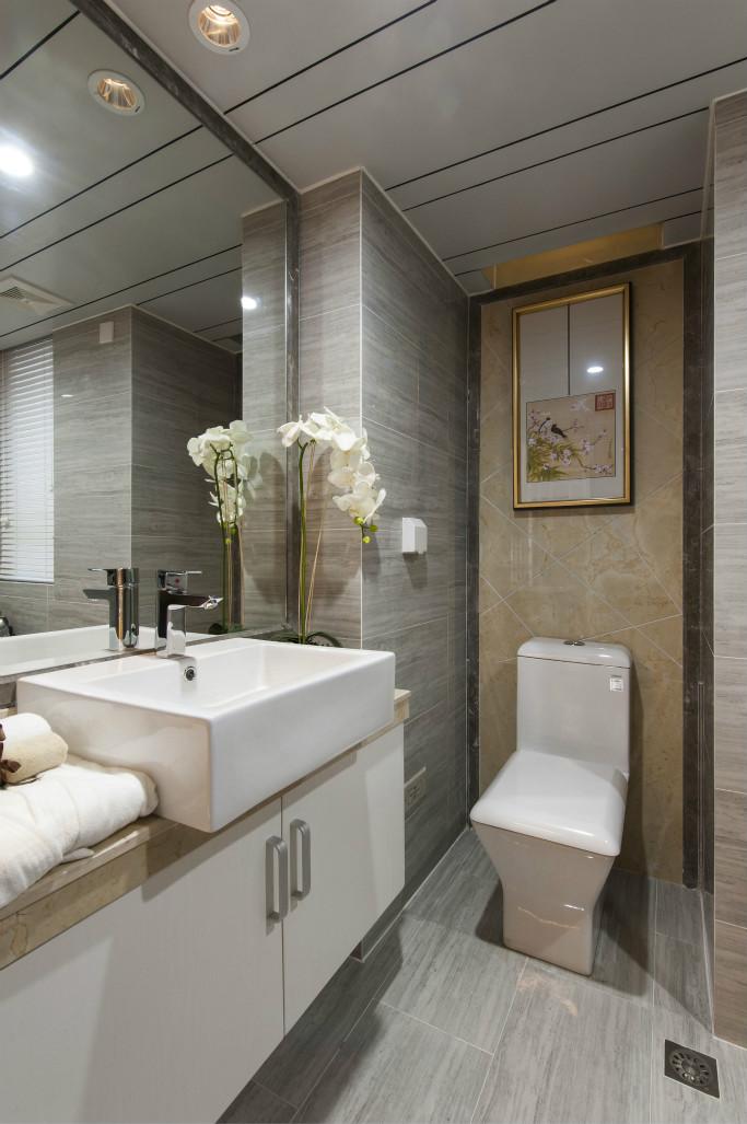 卫浴室的四周背景墙以及地面都是以大块长形瓷砖为铺贴,搭配上白色瓷质的家居简约而时尚
