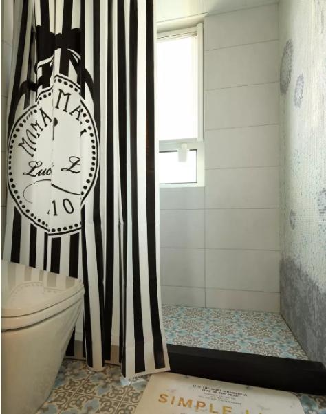 卫生间比较小,用个性黑白条纹窗帘作为遮挡水,墙面采用的简约白色方型瓷砖。空间上明亮大气。