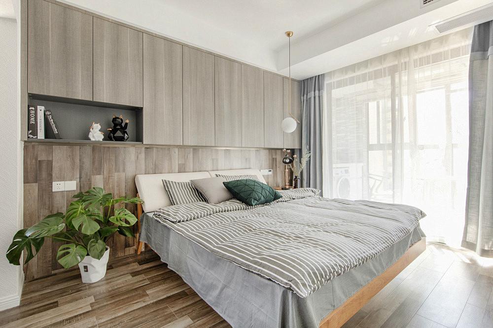 卧室布局也比较简约一些,衣柜是嵌入式的布局,床头柜和床都是原木风,搭配小格子床上用品,很清新,