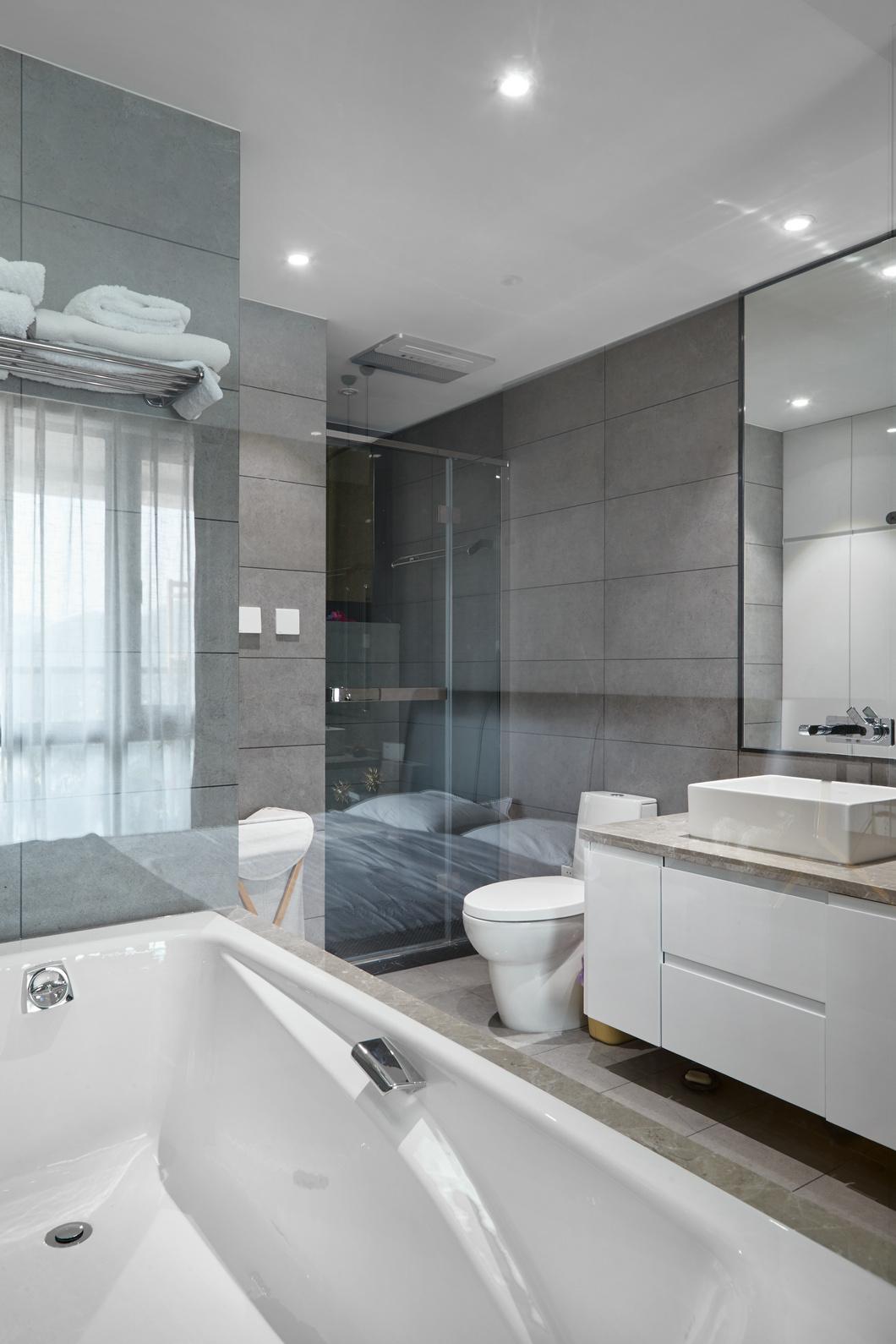 卫浴室的四周以米色的大块瓷砖为铺贴,配上简洁的白色的家居,加上顶面简洁白色方块的顶面吊顶,简洁为敞亮