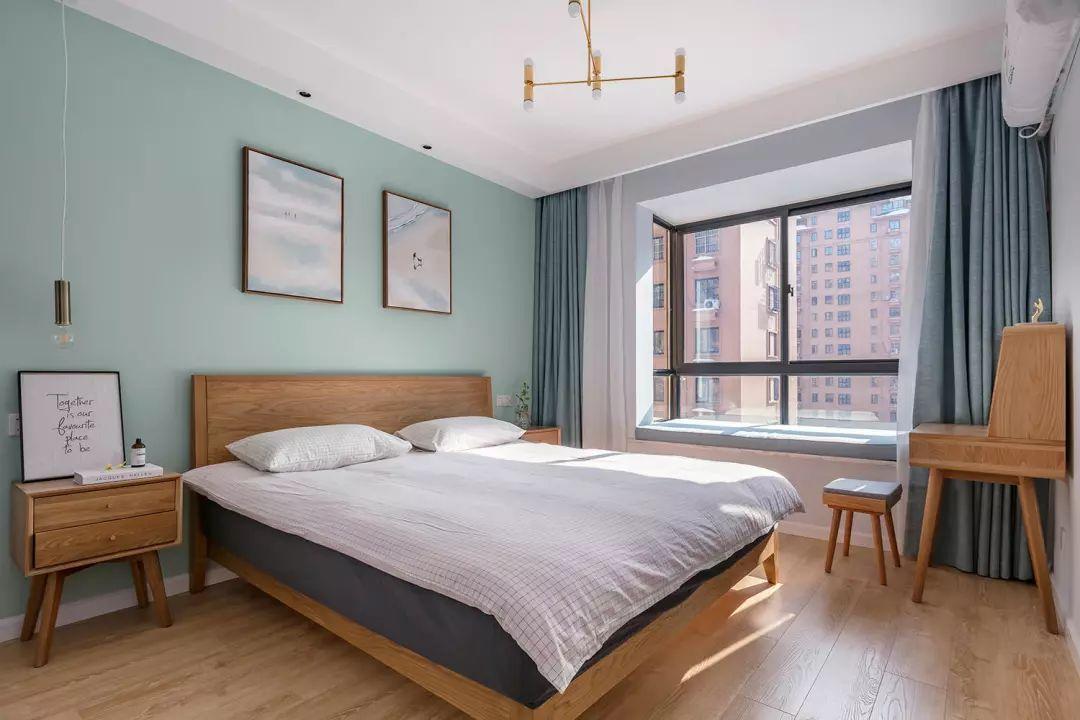 主卧木色地板与木质家具,搭配蓝绿色背景墙与窗帘,简约设计感的铜色吊灯与背景装饰画提升空间整体颜值。