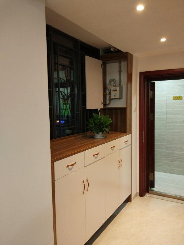 玄关处是一个比较大的鞋柜,白色柜门,原木色台面,经典的颜色搭配。