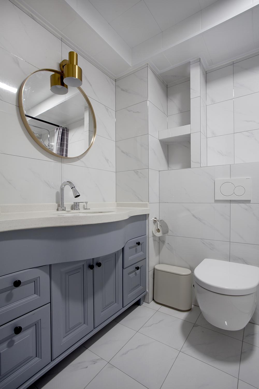 蓝色洗手池在白色背景中显得十分雅致,金属镜面增添室内精致感,壁龛增加空间收纳能力。