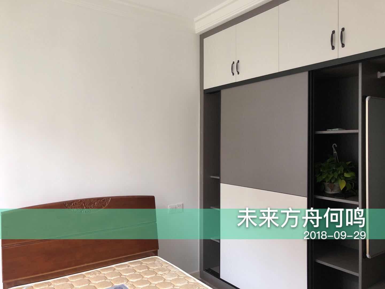 次卧通顶柜体设计,满足收纳的同时具有很好的装饰功能,绿色盆栽点缀了稍显单调的空间。
