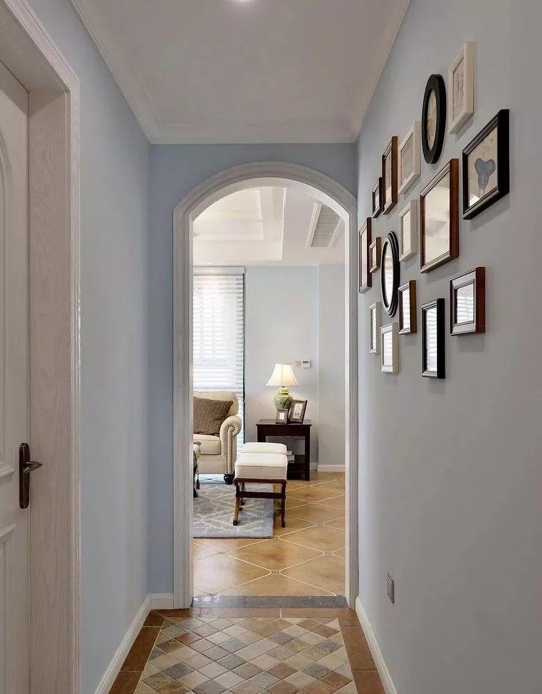 走廊与客厅隔着一个拱形门,采用与玄关一致的仿古马赛克地砖,淡蓝色的墙面上挂上一组的照片墙。