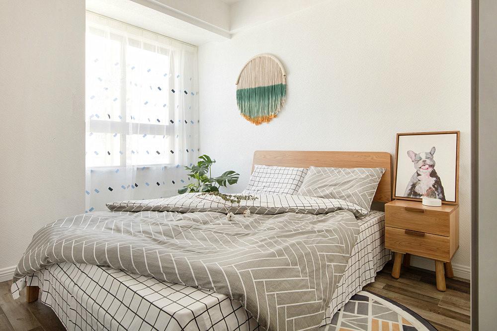 次卧室以木质为主,床头墙悬挂着编制挂画,别有一番分味